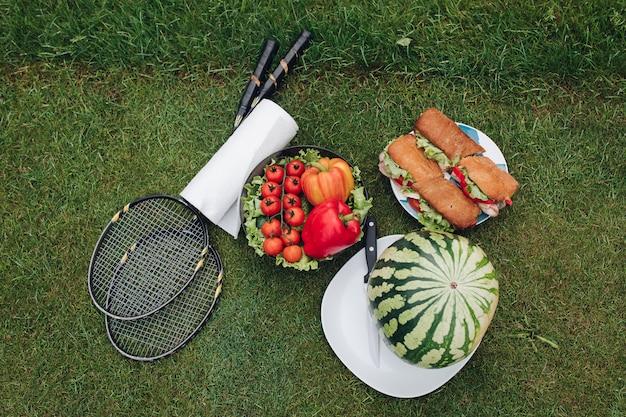 Apetitosa comida fresca lista picnic de verano al aire libre en la vista superior de la hierba verde Foto Premium
