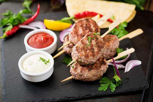 Apetitoso kofta kebab (albóndigas) con salsa y tacos de tortillas en mesa negra Foto gratis