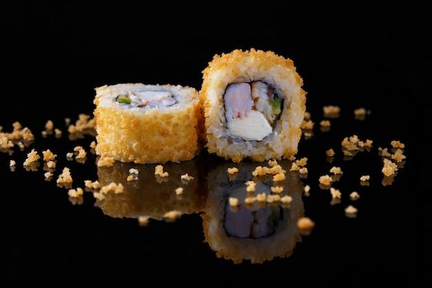 Apetitoso rollo de sushi al horno con pescado sobre un fondo negro con reflejo Foto Premium