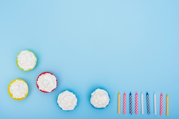 Apetitosos pasteles y velas sobre fondo azul Foto gratis