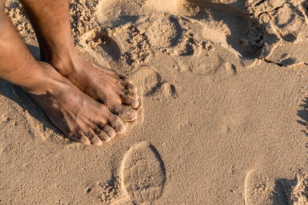 Aplanamiento de pies descalzos sobre la arena Foto gratis