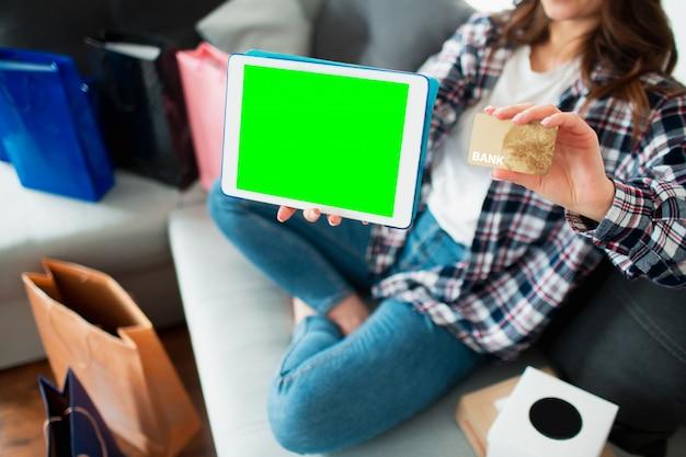 Una aplicación móvil para compras en línea o entrega a domicilio. primer plano de una pantalla de tablet pc y una tarjeta de crédito en manos de una mujer joven. lugar para gráficos y texto, chromakey. Foto Premium