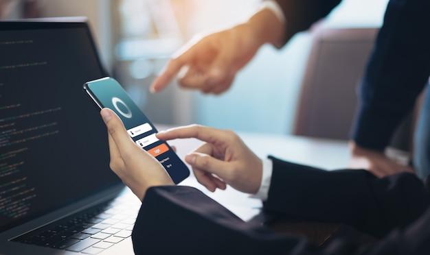 Aplicaciones de diseño de empresaria y equipo en el teléfono inteligente Foto Premium