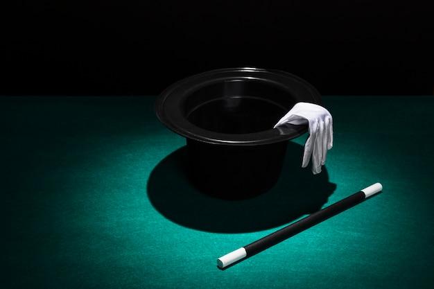 Aplique luz sobre el sombrero de copa con guantes blancos y varita Foto gratis