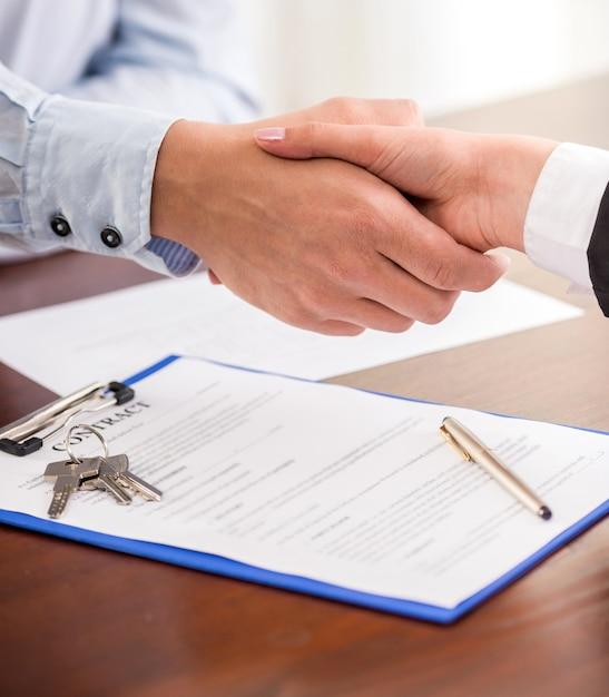 Apretón de manos de un agente inmobiliario y un cliente. Foto Premium