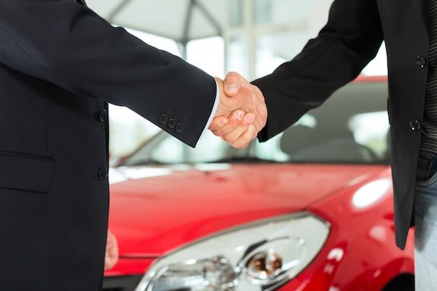 Apretón de manos de dos hombres en trajes con un auto rojo Foto Premium