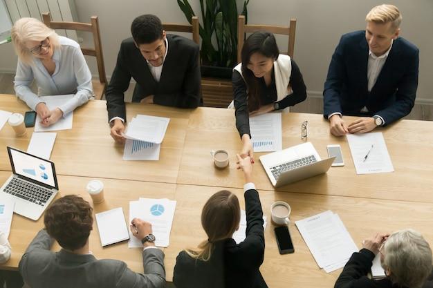 Apretón de manos de las empresarias asiáticas y caucásicas en la reunión de grupo, visión superior Foto gratis
