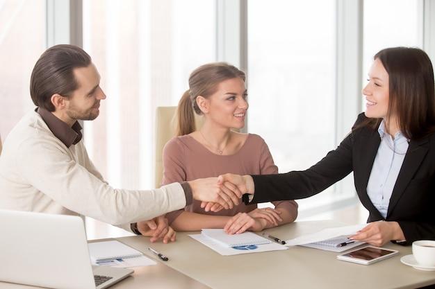 Apretón de manos del hombre de negocios y de la empresaria en la reunión de negocios que se sienta en oficina Foto gratis