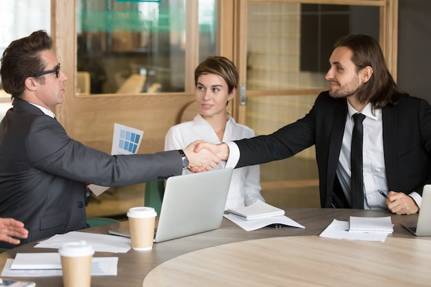 Apretón de manos del hombre de negocios nuevo colega durante la reunión del equipo Foto gratis