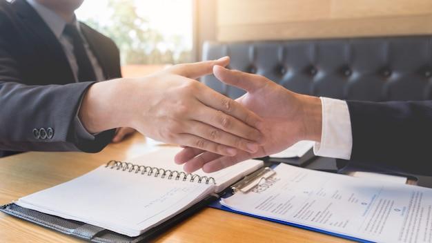 Apretón de manos del jefe y del empleado del negocio después de negociaciones o de entrevista exitosas. Foto Premium