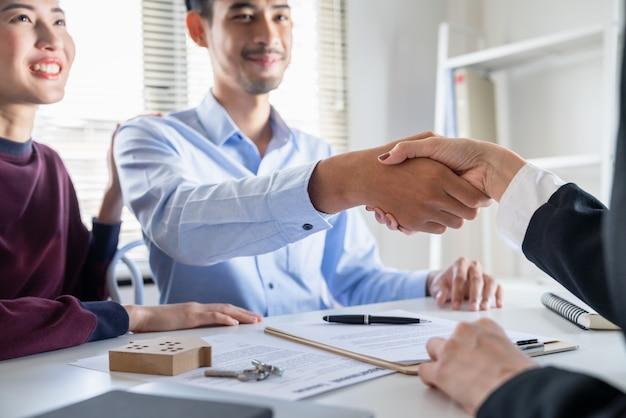 Apretón de manos de la joven pareja asiática con el agente inmobiliario después de llegar a un acuerdo para la compra de su contrato de préstamo hipotecario Foto Premium
