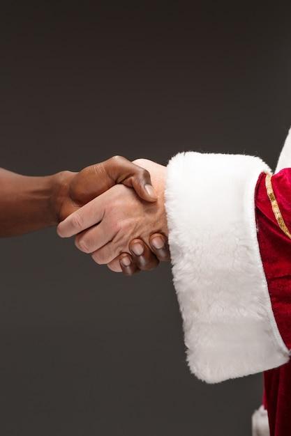 El apretón de manos de la mano de santa claus y la mano del hombre africano. concepto de feliz navidad Foto gratis