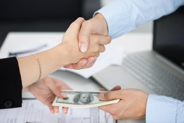 Apretón de manos de mujer y hombre de cerca con el dinero en las otras manos. trato, venalidad, soborno, concepto de corrupción Foto Premium