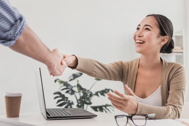 Apretón de manos en la oficina con hermosa mujer Foto gratis