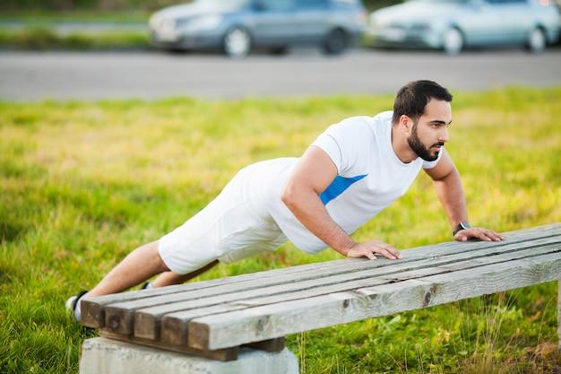 Aptitud. ejercicio de push-up fitness hombre entrenamiento brazos músculos en gimnasio al aire libre Foto Premium