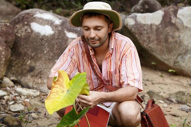 Apuesto biólogo barbudo con sombrero sosteniendo hojas de planta verde, mirando con expresión amable y cariñosa durante sus estudios ambientales en el campo de trabajo. Foto gratis