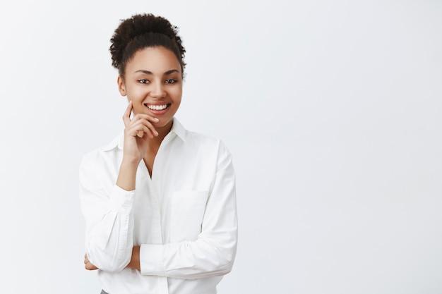 Apuesto emprendedor exitoso de piel oscura escuchando con una sonrisa educada y amigable al empleado, solicitando un nuevo trabajo, entrevistando a la persona, sosteniendo el dedo en la mejilla y sonriendo ampliamente Foto gratis