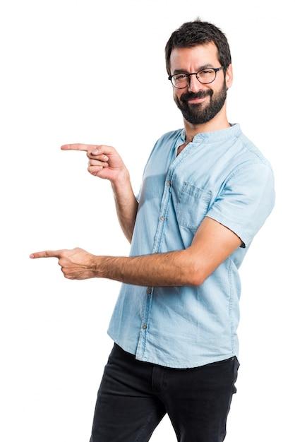 Apuesto hombre apuntando a la lateral Foto gratis