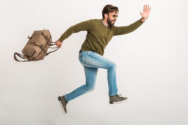 Apuesto hombre barbudo con estilo saltando corriendo aislado vestido con sudadera con bolsa de viaje, jeans y gafas de sol, viajero loco de prisa Foto gratis