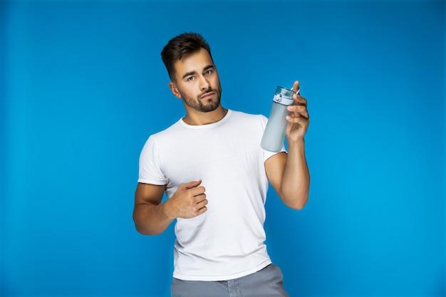 Apuesto hombre europeo en camiseta blanca sobre fondo azul está sosteniendo una botella deportiva en una mano Foto gratis