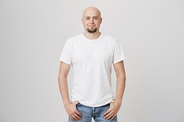 Apuesto hombre de mediana edad calvo con barba vistiendo camiseta blanca casual Foto gratis