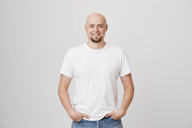 Apuesto hombre de mediana edad calvo sonriente con barba vistiendo camiseta blanca casual Foto gratis