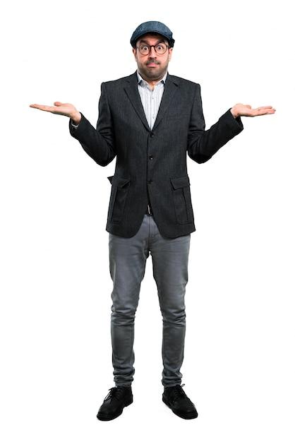 Apuesto hombre moderno con boina y gafas con dudas  9238acfee84