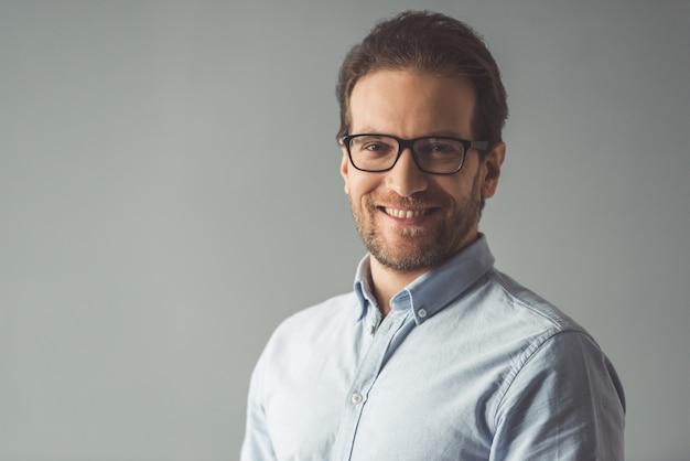 Apuesto hombre de negocios en anteojos está mirando a la cámara. Foto Premium