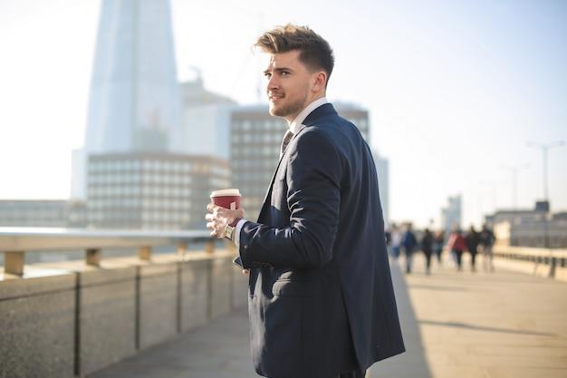 Apuesto hombre de negocios caminando sobre el puente de londres Foto Premium