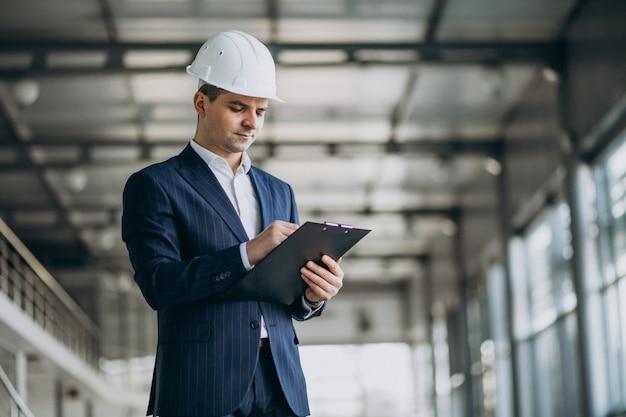 Apuesto hombre de negocios ingeniero en casco en un edificio Foto gratis