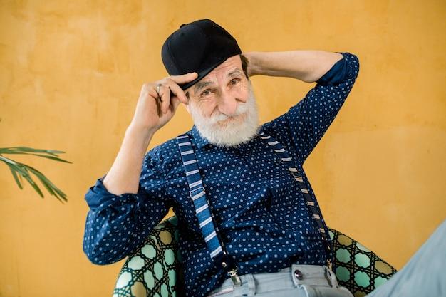 Apuesto hombre senior en camisa azul oscuro, tirantes y gorra hipster negro posando en el estudio, sentado frente a la pared amarilla. elegante moda anciano sobre fondo amarillo Foto Premium