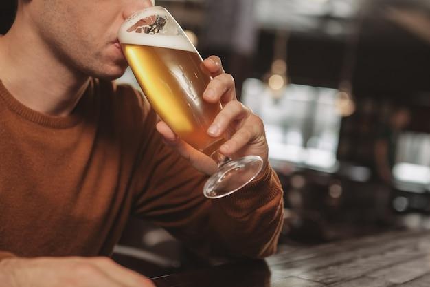 Apuesto joven bebiendo cerveza en el bar Foto Premium
