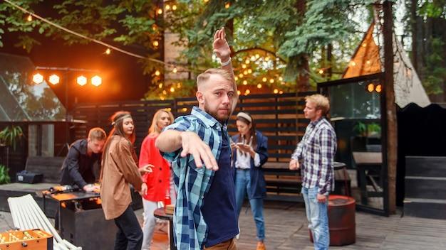 Apuesto joven caucásico de 30 años bailando cerca de la cámara en el fondo de sus amigos en la fiesta en el acogedor jardín de la tarde. Foto Premium
