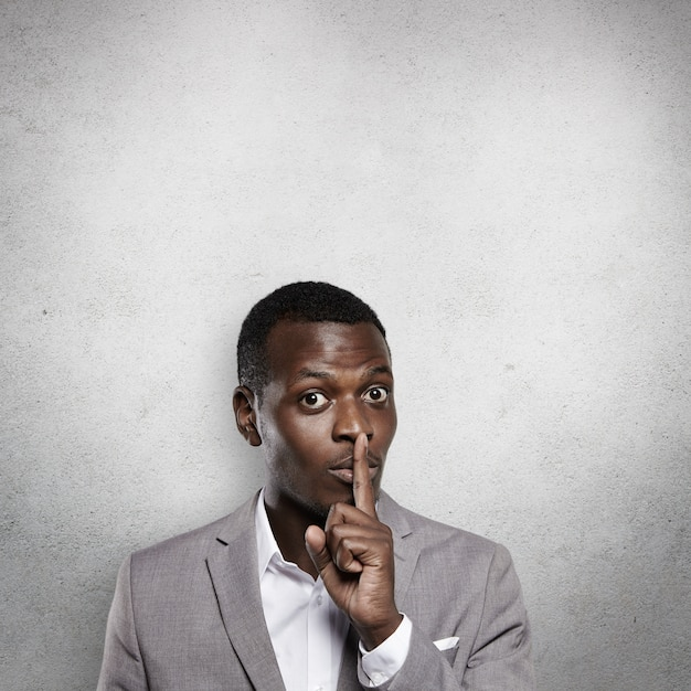 Apuesto joven empresario de piel oscura con traje gris formal que gesticula como si pidiera no contarle a nadie sobre su secreto comercial, se lleva el dedo índice a los labios y dice: shh Foto gratis