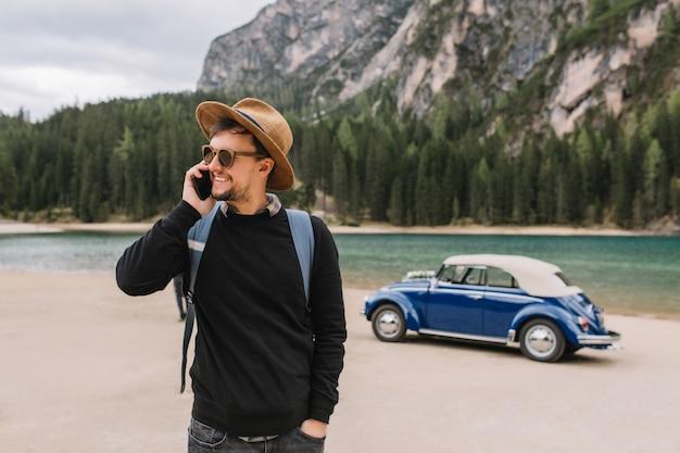 Apuesto joven esperando amigos junto al coche retro en la orilla del río, hablando con ellos por teléfono y mirando a su alrededor Foto gratis