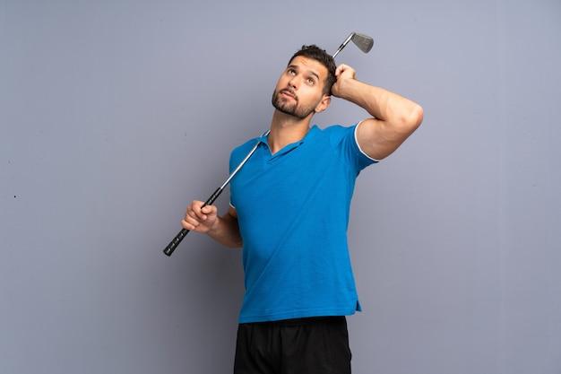 Apuesto joven jugando al golf con dudas y con expresión de la cara confusa Foto Premium