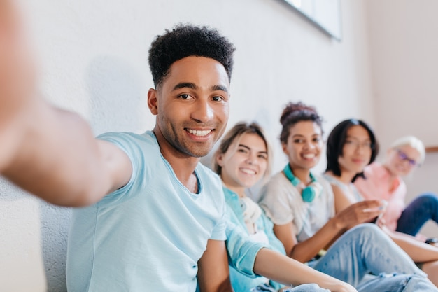 Apuesto joven negro con peinado rizado haciendo selfie con amigos y sonriendo. retrato interior de estudiantes riendo alegres divirtiéndose después de lección y tomando fotos. Foto gratis