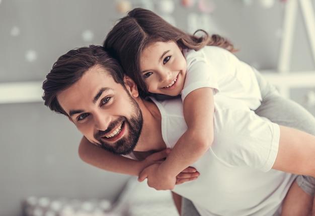 Apuesto joven papá y su pequeña hija linda. Foto Premium