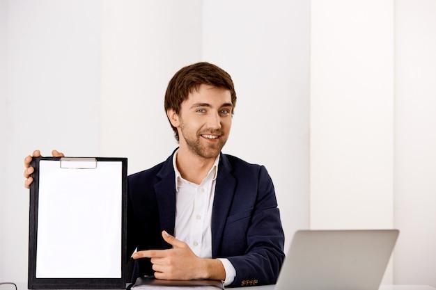 Apuesto joven sonriente y confiado que presenta su carta, sentarse en el escritorio de la oficina, señalar con el dedo en el portapapeles Foto gratis