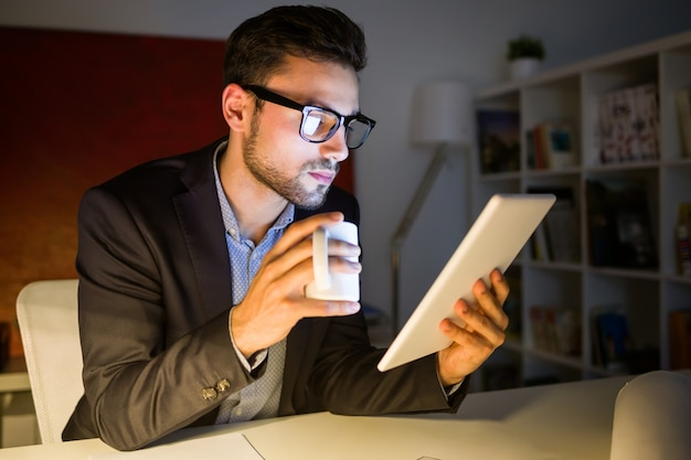 Apuesto joven trabajando con tableta digital en la oficina for Follando en la oficina gratis