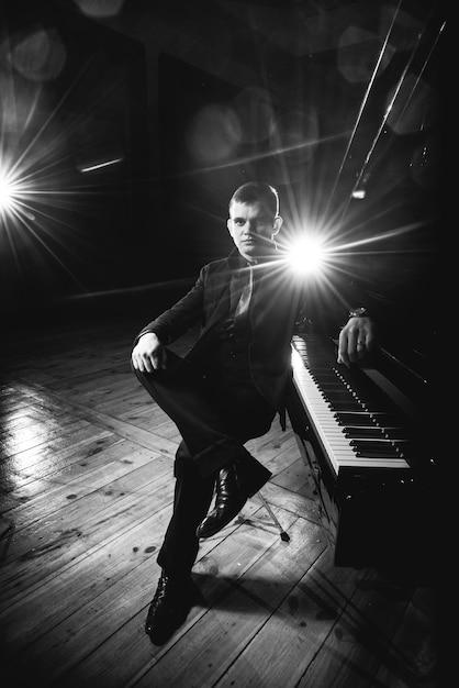 Apuesto joven en traje está sentado al piano y haciendo música de piano.  foto en blanco y negro  238972590ae