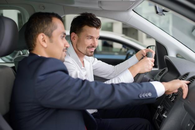 Apuesto joven vendedor mostrando todo el coche. Foto Premium