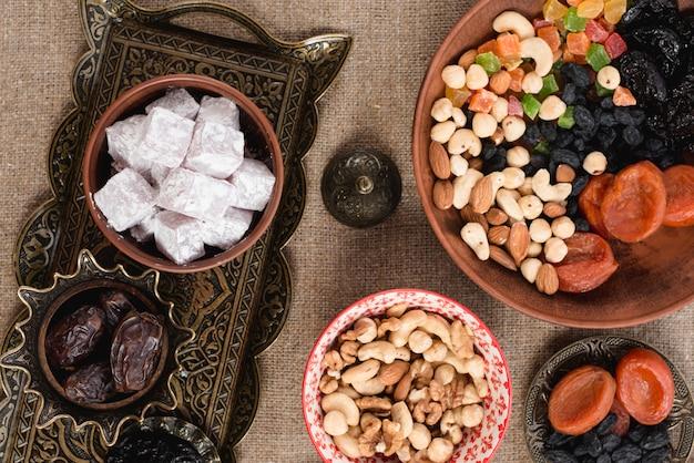 Árabe ramadan lukum; fechas; frutos secos y nueces sobre mesa Foto gratis