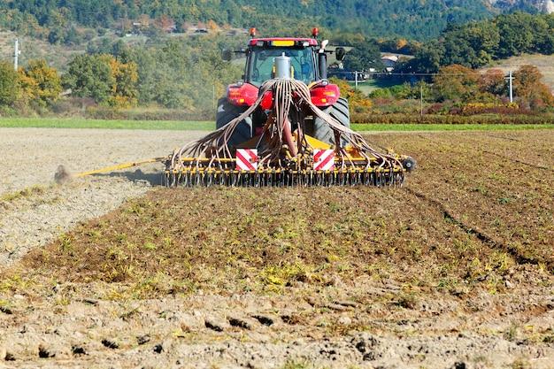 Arando el tractor pesado durante el cultivo agrícola trabaja en el campo con arado Foto gratis