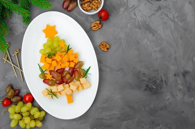 Árbol de navidad de queso con uvas frescas y romero Foto Premium