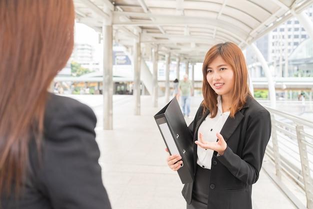 Archivo asiático holdind joven empresaria y mirando colega - concepto de negocio Foto Premium