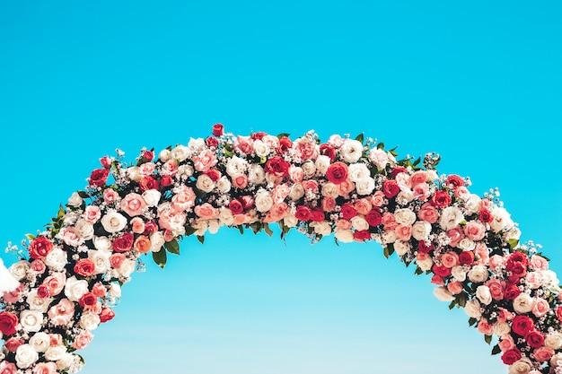 Arco de boda ceremonial en la playa decorado con flores naturales. Foto gratis