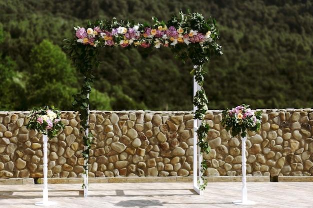 Arco de boda de lujo con hojas exuberantes, rosas delicadas y hortensias púrpuras al aire libre. floristería de la boda Foto gratis