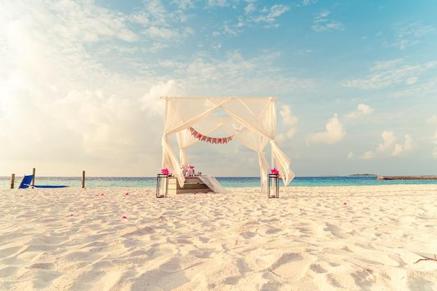 Arco de bodas en la playa con el complejo tropical de maldivas y el mar Foto Premium