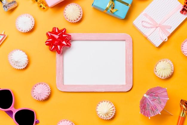 Arco de cinta en marco de madera blanco rodeado de gafas de sol; cajas de regalo y aalaw sobre fondo amarillo Foto gratis